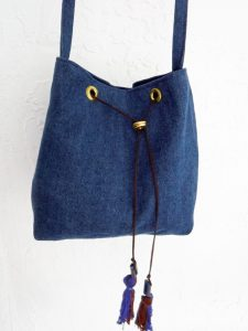 Cross-body denim bucket bag with beaded tassels